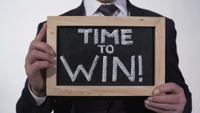Time to win motivation phrase on blackboard in businessman hands, inspiration