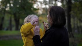 Time together, caring and sensitive mother plays with her charming smiling daughter in autumn park