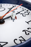 Time travel. Miniature man on the clock royalty free stock image