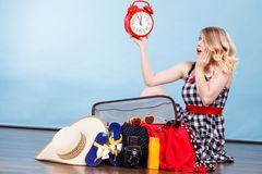 Woman sitting with suitcase holding old clock. Time for travel, being late concept. Terryfied woman sitting on floor with messy packed suitcase holding big red royalty free stock photography
