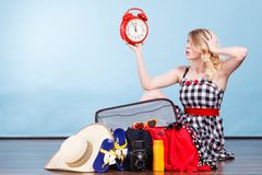 Woman sitting with suitcase holding old clock. Time for travel concept. Happy woman sitting on floor with messy packed suitcase holding big red old clock stock image