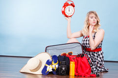 Woman sitting with suitcase holding old clock. Time for travel concept. Happy woman sitting on floor with messy packed suitcase holding big red old clock royalty free stock image