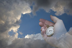 Time Travel at The Speed of Light. A sky with storm clouds at sunset with a hand holding an antique pocket watch stock image