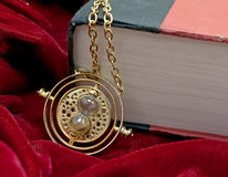 Time Turner Hour Glass Necklace And Book. A large book and Hermione's time turner necklace Royalty Free Stock Photos
