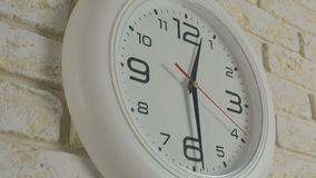 Time twelve hours thirty minutes. Timelapse. Round white clock hanging on brick wall. Time twelve hours thirty minutes. Timelapse. Round white clock hanging on stock footage