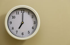 Time for wall clock 7:00. Which hung over the wall Stock Photography