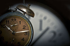 Time will tell. Old rusted alarm clock with another larger clock face in the background Royalty Free Stock Photo