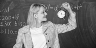 Always on time. Woman teacher hold alarm clock. She cares about discipline. Time to study. Welcome teacher school year. Looking committed teacher complement stock image