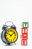 TIME word wooden block arrange in vertical style with black retro alarm clock on white background and selective focus. 1 Royalty Free Stock Photo