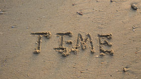 Time written in the sand at the beach waves in the background Stock Photography