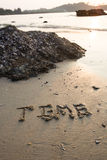 Time written in the sand at the beach waves in the background Stock Image
