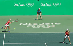 Timea Bacsinszky (L) and Martina Hingis of Switzerland in action during women's doubles final of the Rio 2016 Royalty Free Stock Photo