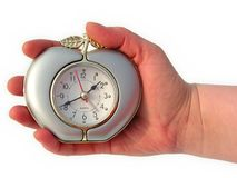 Timekeeper. Hand holding an apple-shape clock stock images