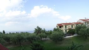Timelappse of tourist cottages near the coast, trees, clouds pass quickly. Halkidiki, Greece stock video footage