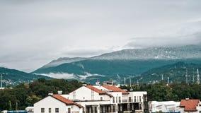 Timelaps, dorpen in de bergen, wanneer het en de zon regent glanst in de herfst De grijze wolken bewegen zich snel over stock videobeelden