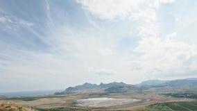 Timelaps, droog meer op een vliegtuig met berg Kara -kara-dag en villiage Koktebel op een achtergrond en gekrulde wolken snel stock videobeelden