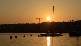 The timelaps of sunset and view on Sliema and sail yacht with Ukrainian flag. Sliema, Malta stock video footage