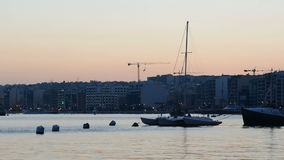 The timelaps of sunset and view on Sliema. And sail yacht with Ukrainian flag, Sliema, Malta stock video