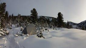 Timelaps tält i en snöig skog på solnedgången stock video