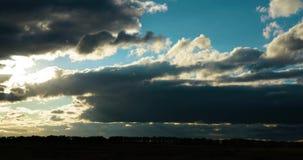 Timelaps van het bewegen van pluizige wolken in de avond hemel tijdens zonsondergang in weide stock footage