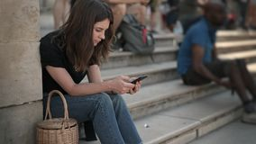 Timelapse της γυναίκας με τη συνεδρίαση smartphone στα σκαλοπάτια κοντά στο Λούβρο του Παρισιού απόθεμα βίντεο