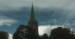 Timelapse που βλασταίνεται του πύργου εκκλησιών με τα δέντρα στο πρώτο πλάνο απόθεμα βίντεο