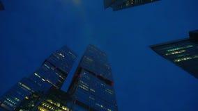 Timelapse Σύγχρονοι ουρανοξύστες της ασυνήθιστης μορφής φιαγμένης από γυαλί Κατώτατη όψη Ηλιοβασίλεμα φιλμ μικρού μήκους