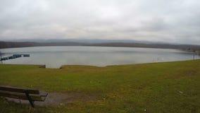 Timelapse του μόνου πάγκου στην όχθη της λίμνης, πουλιά που κολυμπά, κατάθλιψη, λυπημένες μνήμες απόθεμα βίντεο
