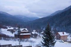 Timelapse деревянных коттеджей в долине горного села окруженной с coniferous лесом и снежными горами Быстрый взгляд сток-видео