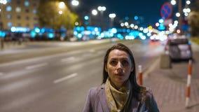 Timelapse женщины стоя все еще на толпить выравниваясь улице пока нерезкость быстроподвижных автомобилей двигает за ей акции видеоматериалы