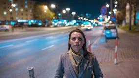 Timelapse женщины стоя все еще на толпить выравниваясь улице пока нерезкость быстроподвижных автомобилей двигает за ей сток-видео