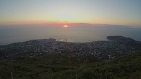 Timelapse захода солнца океана, красивый вид на городе вечера от горного пика акции видеоматериалы