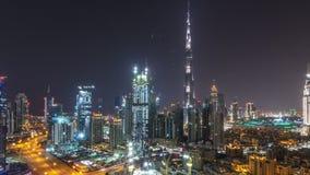 Timelapse aéreo del paisaje urbano en la noche con el centro de la ciudad moderno iluminado de la arquitectura adentro de Dubai,  almacen de metraje de vídeo
