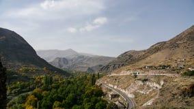 Timelapse av bergvägtrafik Sikt till det slingrande med bilar mot bakgrund field blåa oklarheter för grön vitt wispy natursky för lager videofilmer