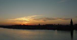 Timelapse av Kungsholmen horisont i Stockholm Gult och rött solljus som att glo över hamnen arkivfilmer