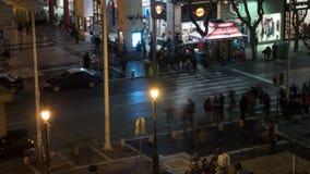 Timelapse av nattstaden med den upptagna genomskärningen med övergående bilar och gångare stock video