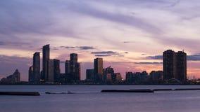 Timelapse av solnedgången med ljusa himmel och moln över cityscape vid Lake Ontario arkivfilmer