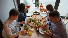 Timelapse av unga vänner som äter en pizza på pizzerian, samtal och att skratta stock video