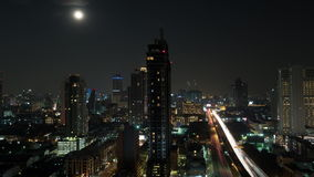 Timelapse of Bangkok night life, Thailand. Timelapse shot of night in Bangkok. Moon rising over Thailand capital. Cityscape with illuminated buildings and busy stock footage