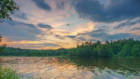 Timelapse of cloudy sunrise over forest lake stock video footage