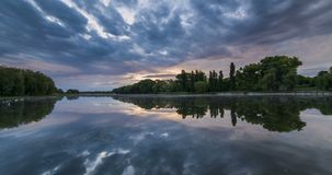 Timelapse of beautiful cloudy sunrise in a lake with reflection. stock footage
