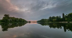Timelapse of beautiful cloudy sunrise in a lake with reflection. stock video footage