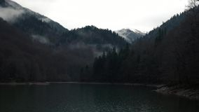 Lake With White Smoke Stands Amid High Mountains. Timelapse - Beautiful Lake With White Smoke Stands Amid High Mystical Mesmerizing Mountains With Overgrown stock footage