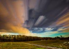 Timelapse-Bewegung von Wolken in Richtung zum Holz über einem Feld von Ernten Lizenzfreies Stockfoto