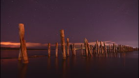 Timelapse of a bright starry night with reflection on water, clouds and enigmatic wooden pillars Royalty Free Stock Photo