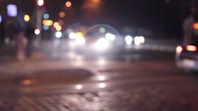 Timelapse a brouillé des personnes traversant la rue dans la ville la nuit avec les voitures, le feu de signalisations et les bât banque de vidéos