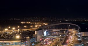 Timelapse of busy car traffic in night illuminated city. Timelapse night shot of intense car traffic on the road with overpass and full multilevel parking lot stock video footage