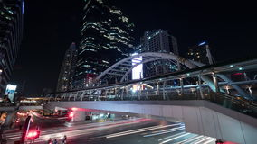 Timelapse of busy road and pedestrian overpass in night Bangkok stock video