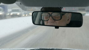 Timelapse of car traveling in urban streets. Timelapse of traveling by car in winter city. Senior driver in glasses reflecting in rear-view mirror stock footage