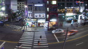 Timelapse of cars and pedestrians traffic on night road in Seoul, South Korea. SEOUL, SOUTH KOREA - OCTOBER 22, 2015: Timelapse panning and wide angle shot of stock footage